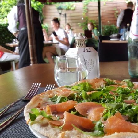 My Salmon pizza with arugula on Garden Risto's patio seating