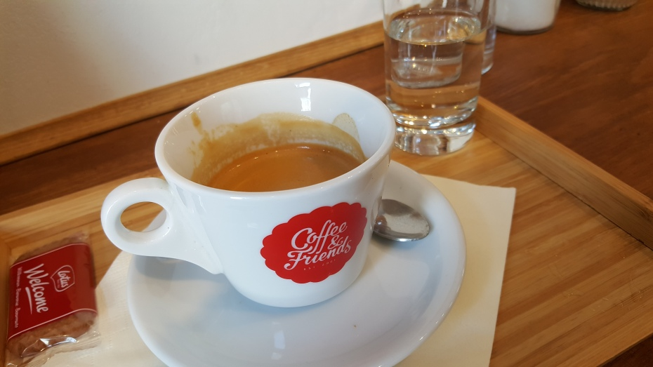 A double espresso in a small white mug with the Coffee & Friends logo